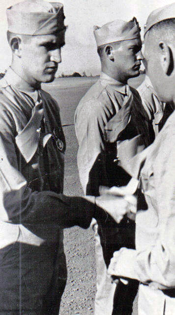 Davis receives the Purple Heart medal for wounds sustained on Saipan. The regiment's commander, Colonel Walter Jordan, is shaking his hand.