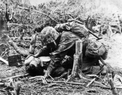 A wounded marine on Peleliu is given a drink of water. Temperatures of over 100 degrees made the suffering of the wounded even worse.