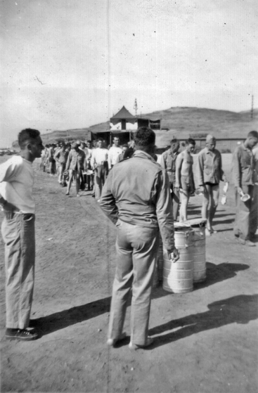 Captain Irving Schechter (at left) and Lieutenant Roy Wood (back to camera) watch Able Company line up for chow during exercises at Aliso Beach.