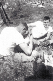 George Smith pulls cactus spines out of his knee at Camp Pendleton. They had set up an ambush in a cactus when George was in turn ambushed by a rattlesnake's rattle. Although painful, spines beat being bitten.