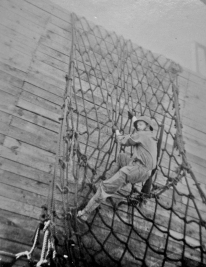 A Marine climbs down an obstacle meant to simulate climbing a net down the side of a ship.