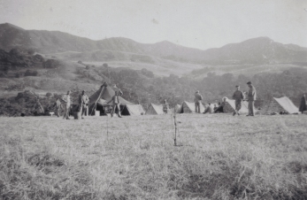 """Semaphore practice in front of the Company tent. Good shot of the California hills–a straight rise of 1000 feet or more, and all of our problems seem to takeplaceon top of these sons of guns. Certainly makes for beautiful scenery, though."""