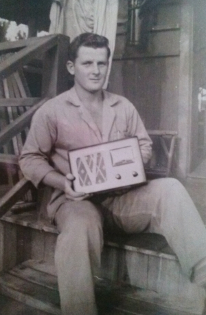 """Sitting on back porch of our hut with radio I won in Bingo game. From March 1946, Hilo, Hawaii."""