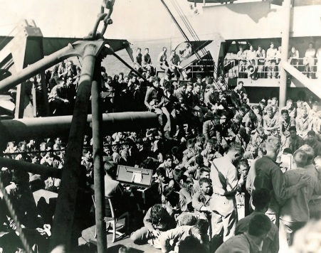 Marines leave Iwo Jima aboard the USS Newberry. Abbott is one of the men sitting in front of the organ.