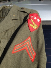 "What makes this blouse unusual is the patch above the corporal chevrons. As part of the 24th Marines, Polus would have had a blouse with the Fourth Marine Division patch starting in the spring of 1944. The patch above is for the 5th Marine Amphibious Corps (VAC). While the 4th Marine Division was part of VAC, wearers of this patch usually served with its headquarters units. Asack was probably issued this blouse while recovering from his Saipan wounds, though he was technically ""on detached duty"" he was in reality recovering in a hospital."