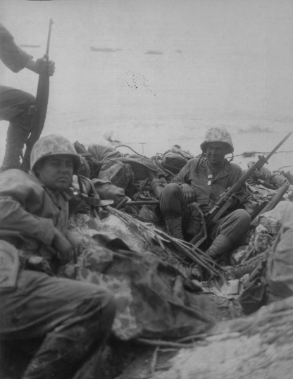 When assault troops came ashore, they dropped their excess gear. Someone had to stay and guard it. PFC Harold Rediske (right) camps out with Baker Company's 782 pile on the beach. Official USMC photo