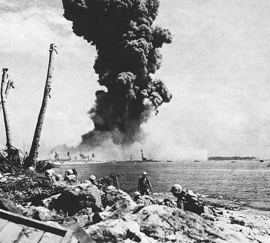 A torpedo warhead storage bunker detonates on Namur. Note the landing craft approaching the beach. Photo taken from Roi Island.