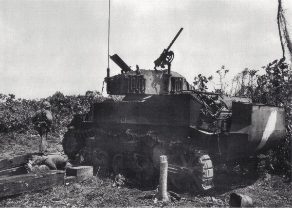 "Captain Denig's tank, ""Hunter,"" after the battle. Note the Japanese body at left."