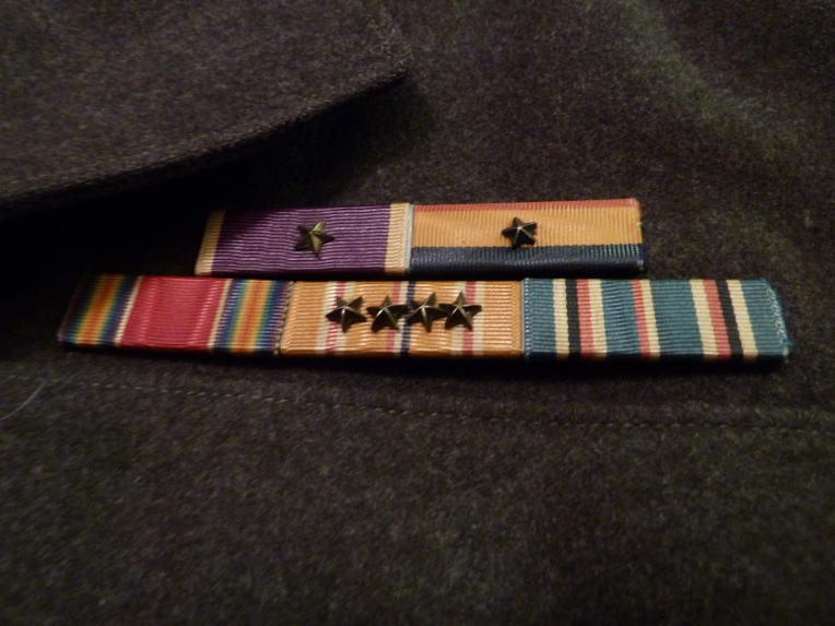 "Corporal Jettenberg's ""fruit salad"" of medals earned in two and a half years of service. He has the Purple Heart with Gold Star (wounded twice), the Presidential Unit Citation, WWII Victory Medal, Asiatic-Pacific Campaign medal (each star denotes one campaign) and the American Theater ribbon."