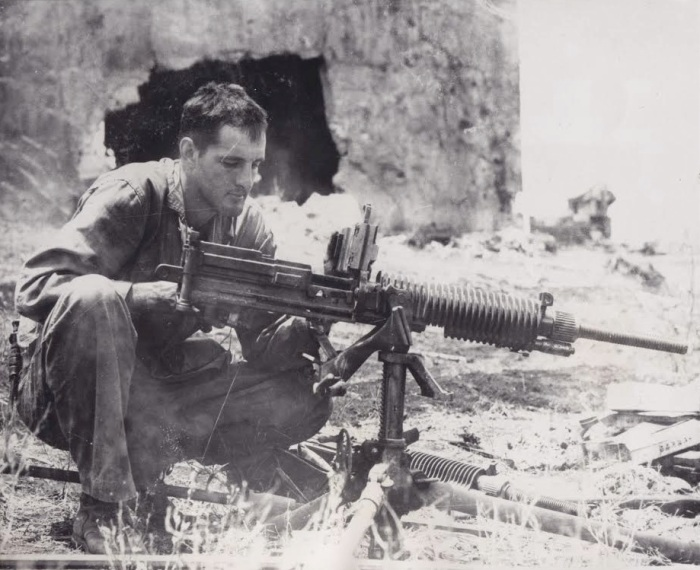 """BOSTONIAN EXAMINES CAPTURED JAP GUN. 1st Lt. Endecott Osgood of 116 Commonwealth Ave, Boston, Mass. examines a captured Jap machine gun which his platoon of scouts took from 46 Japs which they captured on Saipan in the Marianas."""