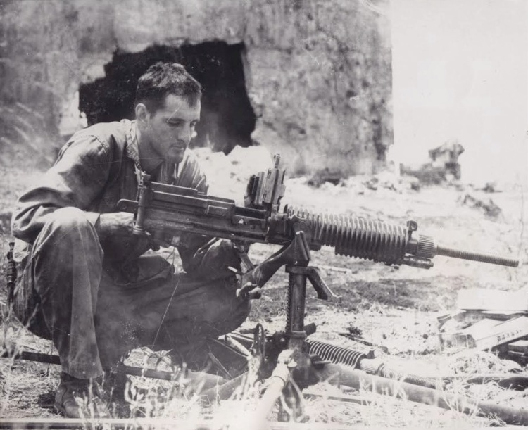 """""""BOSTONIAN EXAMINES CAPTURED JAP GUN.  1st Lt. Endecott Osgood of 116 Commonwealth Ave, Boston, Mass. examines a captured Jap machine gun which his platoon of scouts took from 46 Japs which they captured on Saipan in the Marianas."""""""