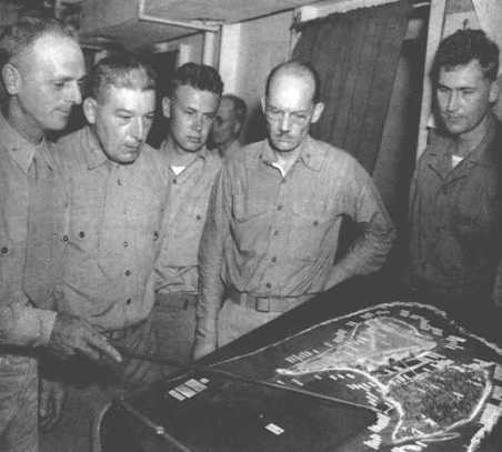 Colonel Franklin Hart (left), commanding officer of the 24th Marines, briefs his officers on the way to Roi-Namur. Major Schultz is standing at far right.