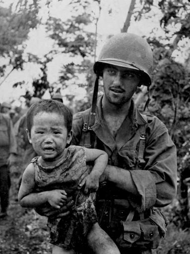 """PFC Dominick Domeo of Chicago, IL, carries an abandoned child he found in a field near his battalion command post."" July 4, 1944. US Army Photo; Laudansky."