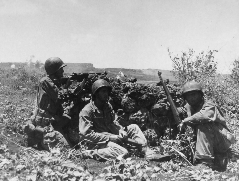 """""""Three US soldiers crouch behind rock pile on one of the hills new Nafutan Ridge overlooking cane fields."""" June 21,1944. US Army Photo; Gurtcheff."""