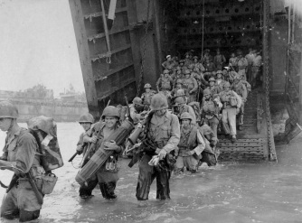 """""""U. S. Army reinforcements emerge from LST and start across coral reef to beach."""" US Army Photo; Laudansky."""
