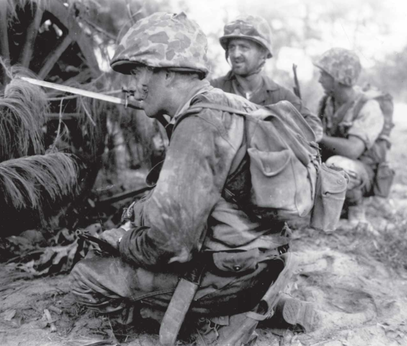 Tired Marines catch their breath in the cover of a Saipanese wagon.