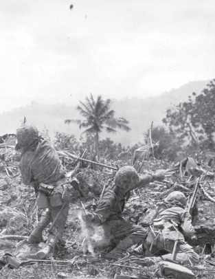 Marines of the 2nd Marine Division (note the camouflage HBTs on the man at left) toss grenades at the enemy.
