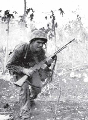 A Marine with a BAR advances under fire.