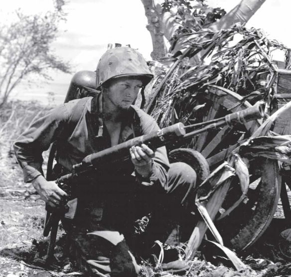 Another Marine huddles behind a wagon (possibly the same as in the previous photo). He is armed with the M1A1 flame thrower.
