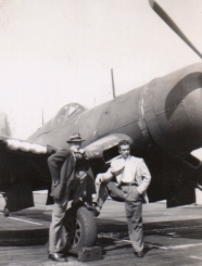 Two individuals in civilian duds posing with an F4-U Corsair.