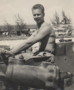 """Taken in the Marianas, Tinian. I ran this bull-dozer for a month there. A scratch on the negative makes it look like I have scars on my face."" Unknown individual."