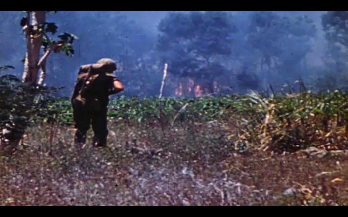 A Marine advances towards a burning treeline on Saipan. Still from USMC combat camera footage.