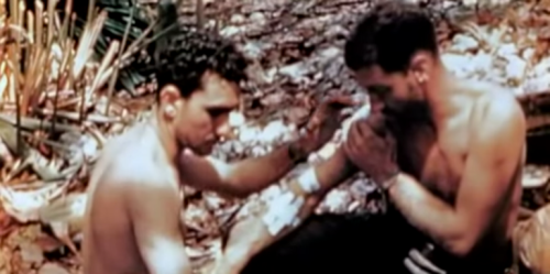 A corpsman treats a Marine with multiple arm wounds.
