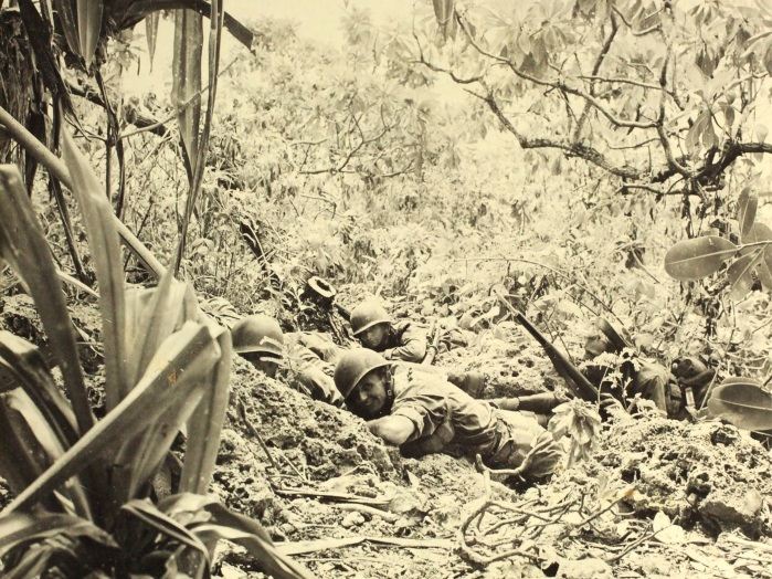 A 27th Division patrol pinned down by sniper fire on Saipan. Soldier in foreground still manages to smile for the camera. US Army photo.