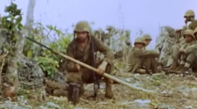 """Marine poses with an """"idiot stick"""" - a bayonet affixed to a long pole. The original owner has carved his spear to resemble a rifle stock."""