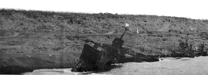 A wrecked Japanese ship lies off the Boat Basin. The ground, TA 166D-E, was Able Company's area of operations on D+1.