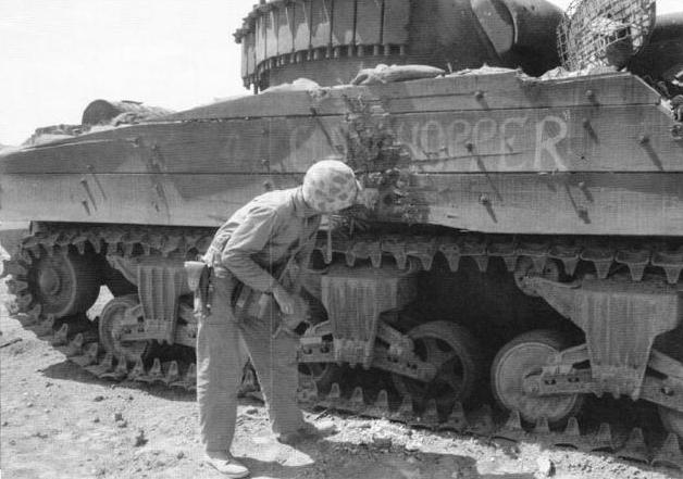 "A curious Marine inspects the wound that killed M4 Sherman ""Clodhopper,"" of C/4th Tank Battalion."
