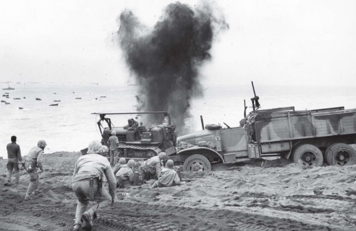 A bursting shell sends this Marine working party scurrying for cover. Official USMC photo.
