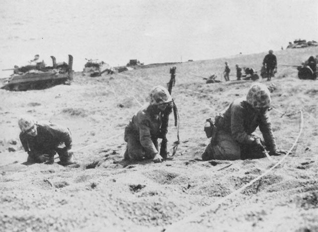 Engineers clear mines, marking safe passages with white tape.