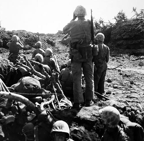 A Fourth Marine Division officer checks on a distant target through binoculars. USMC photo.