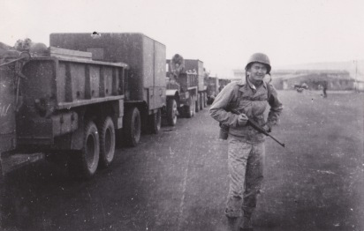 "An officer poses at the head of another convoy. The vehicles appear to be the 2.5 ton ""6x6"" trucks made by International Harvester."