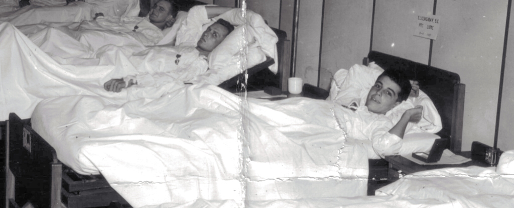 PFC Elissagaray recuperates in a hospital on New Caledonia in 1944. He has just received a Purple Heart medal, which is pinned to his bedsheets.