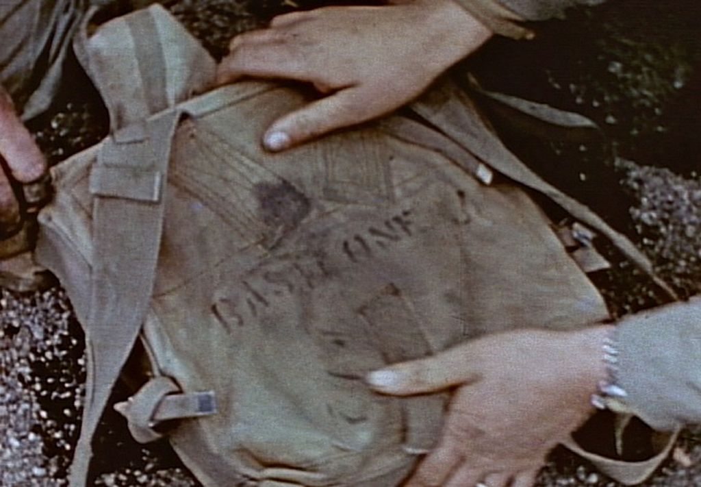 Marines display John Basilone's pack for the camera. In a following shot, a shirt from this pack is given to a corporal from Basilone's hometown. Still from USMC combat carmera.