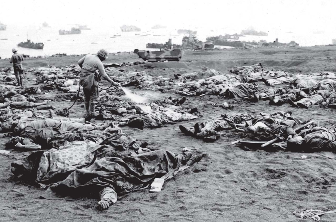 Marine dead awaiting burial on Iwo Jima. The man at center is spraying disinfectant to keep flies away. USMC photo.