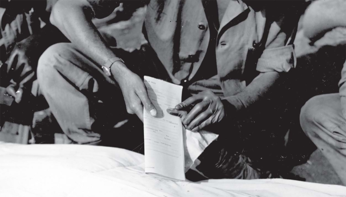 Fingerprinting a dead Marine. Taking prints helped confirm the identity of the deceased: a very low percentage of American casualties on Iwo went unidentified.