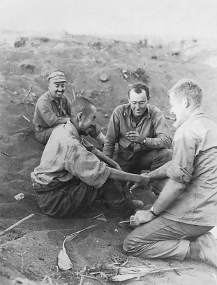 """Oscar - the Jap - was a cook for the aviators on Iwo. Majors Schechter, Cokin, and I captured [Oscar] when we were out on reconnaissance one day."" Oscar is being interviewed by the R-2 (Major Hanson), a division interpreter (Lt. Johnson) and an unknown member of the R-2 section."