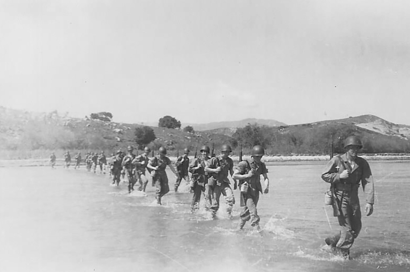 Webster heads a patrol crossing a shallow river. Date and location unknown, possibly while training at Camp Pendleton.