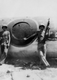 "Two Marines pose by the ""meatball"" insignia, which doubled as the Betty's entry hatch."
