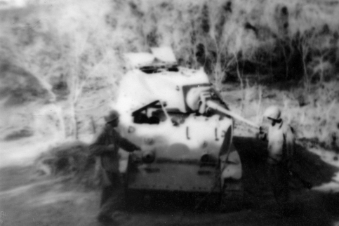 Curious Marines inspect an abandoned American M5 light tank.