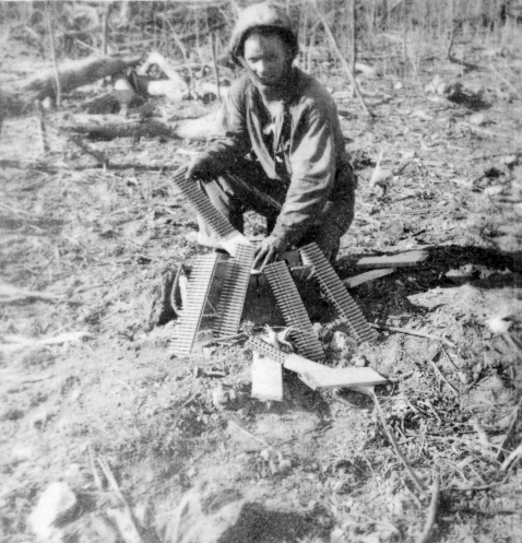 A Marine displays a professional interest in his adversary's equipment, inspecting a wooden box of Japanese MG ammo.