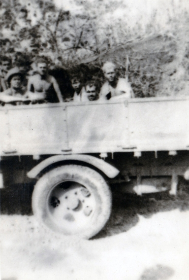 "After the battle of Namur, 1/24 was ordered to clean up its battlefield. ""We found an old flatbed truck and managed to get it started. We got the bright idea to use it to haul bodies."" Disgust is evident on every face, despite the blurred focus."