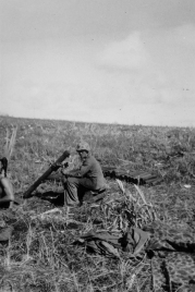 A less sociable Marine with his mortar. Although themortar's muzzle cover is on, a stack of ammunition is close at hand.