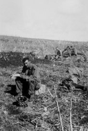 A mustachioed man, possibly one of the platoon NCOs, sits with pencil and pad.