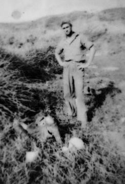 An unidentified Marine stands over the dead Japanese seen in the previous picture.