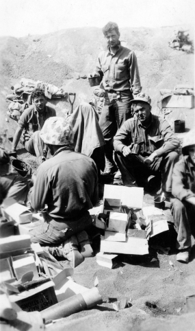 """Chow down on Iwo Jima."" These 1/24 Marines are lucky to have found boxes of coveted 10-in-1 rations."