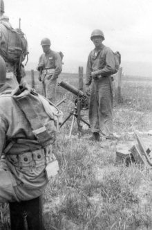 A .30 caliber machine gun on its tripod in the field.